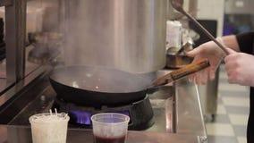 Cocinero en verduras de una fritada del fuego y pedazos de carne abiertos grandes almacen de metraje de vídeo