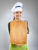Cocinero feliz de la mujer que lleva a cabo a un tablero Imágenes de archivo libres de regalías