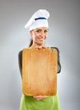 Cocinero feliz de la mujer que lleva a cabo a un tablero Fotografía de archivo libre de regalías