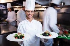 Cocinero feliz que le presenta las placas de la comida Foto de archivo
