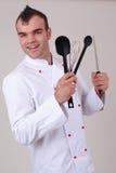 Cocinero feliz que sostiene los diversos utensilios de la cocina Imagen de archivo