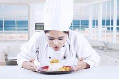 Cocinero Finishing un plato en la placa Imagen de archivo libre de regalías
