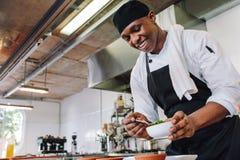 Cocinero gastrónomo que cocina en una cocina comercial imagenes de archivo