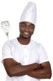 Cocinero hermoso africano con los utensilios de la cocina Fotografía de archivo