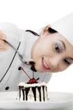 Cocinero hermoso que adorna una torta dulce Fotos de archivo libres de regalías