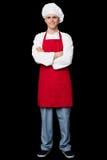 Cocinero hermoso que presenta con los brazos cruzados foto de archivo