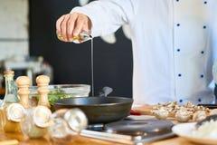 Cocinero irreconocible Frying Mushrooms fotografía de archivo libre de regalías