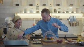 Cocinero joven con el chef de repostería que usa el equipo que añade humo o el vapor al plato para una porción encantadora almacen de metraje de vídeo