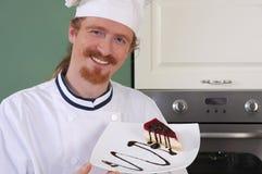 Cocinero joven con el pedazo de torta Imagen de archivo libre de regalías
