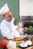 Cocinero joven divertido con bróculi Fotos de archivo libres de regalías