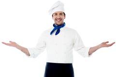 Cocinero joven elegante que acoge con satisfacción a huéspedes imagen de archivo