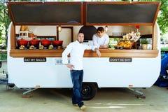 Cocinero joven hermoso que mira la cámara en un camión de la comida Imágenes de archivo libres de regalías