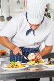 Cocinero que adorna el plato con mayonesa Imagenes de archivo