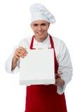 Cocinero joven que mira la pizza deliciosa fotos de archivo