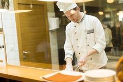 Cocinero joven que prepara una comida Imagen de archivo libre de regalías