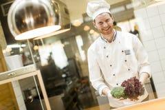 Cocinero joven que prepara una comida Fotos de archivo