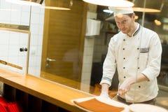 Cocinero joven que prepara una comida Foto de archivo
