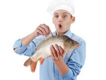 Cocinero joven que sostiene una carpa de los pescados en el fondo blanco Fotografía de archivo
