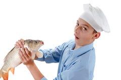 Cocinero joven que sostiene una carpa de los pescados en el fondo blanco Foto de archivo libre de regalías