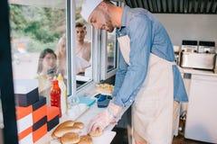 cocinero joven sonriente que trabaja en el camión de la comida mientras que situación de la gente joven foto de archivo