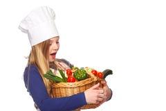 Cocinero menor que sostiene una cesta con los vehículos Imagenes de archivo
