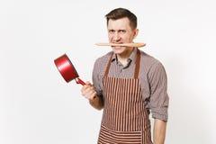 Cocinero o camarero agresivo del hombre en el delantal marrón rayado, camisa que sostiene la cuchara stewpan, de madera vacía roj imágenes de archivo libres de regalías