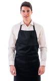 Cocinero o camarero joven que lleva el delantal negro aislado Imagenes de archivo