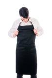 Cocinero o camarero joven que lleva el delantal negro aislado imágenes de archivo libres de regalías