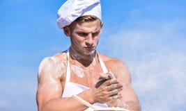 Cocinero o cocinero con los hombros musculares atractivos y pecho cubierto con la harina Concepto del panadero Cocinero del cocin foto de archivo libre de regalías