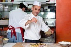 Cocinero ocupado en vías de la preparación de la pizza foto de archivo