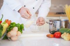 Cocinero Pouring Milk Into un cuenco Imagen de archivo