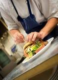 Cocinero Preparing Gourmet Hamburger Fotos de archivo libres de regalías