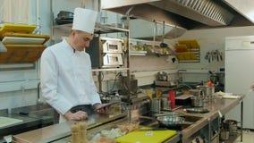 Cocinero principal que usa la tableta mientras que cacerola preparada auxiliar joven metrajes