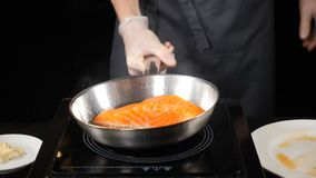 Cocinero profesional en cocinar del restaurante Concepto de cena fino Manos masculinas que sostienen el sartén con el prendedero  metrajes