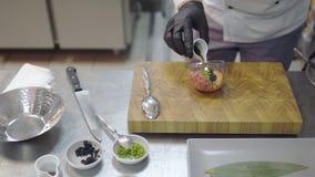 Cocinero profesional en los guantes de goma negros que preparan el plato con el atún y los salmones crudos en primer moderno de l almacen de video