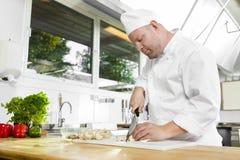 Cocinero profesional que prepara verduras en cocina grande Fotos de archivo