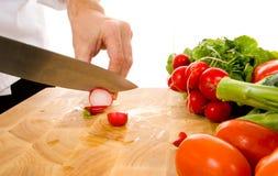 Cocinero profesional que rebana el rábano Foto de archivo