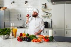Cocinero profesional que se coloca en su cocina brillante grande y que sostiene el tomate rojo fresco Fotos de archivo libres de regalías
