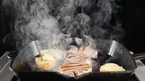 Cocinero profesional que trabaja en cocina del restaurante Patata y carne en parrilla Humo blanco sobre la comida deliciosa Tirad metrajes