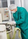 Cocinero In Protective Workwear que usa las pastas de los espaguetis Foto de archivo