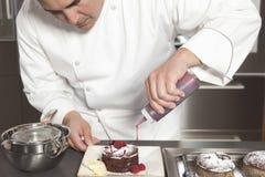 Cocinero Puts Finishing Touches en la torta de chocolate en la encimera fotografía de archivo