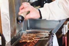 Cocinero que añade la pimienta al Bbq Imagenes de archivo