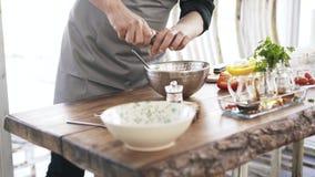 Cocinero que añade la sal y las especias a una ensalada vegetal y que las mezcla metrajes
