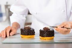 Cocinero que acaba una torta Imagen de archivo libre de regalías