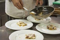 Cocinero que adorna el plato delicioso Fotografía de archivo