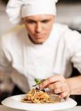 Cocinero que adorna la ensalada de pasta con las hojas herbarias Fotografía de archivo libre de regalías