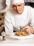 Cocinero que adorna la ensalada de pasta con las hojas herbarias Foto de archivo
