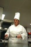 Cocinero que afila los cuchillos Foto de archivo