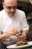Cocinero que agrega el condimento al plato en cocina imagenes de archivo