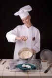 Cocinero que agrega el huevo Foto de archivo libre de regalías